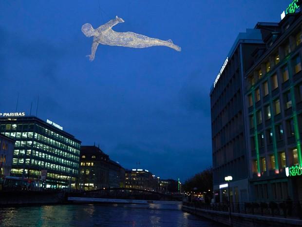Uma escultura é suspensa na praça Bel Air em Genebra, na Suíça. A instalação 'Voyageurs', do artista francês Cedric Le Borgne, faz parte do Festival de Luz de Genebra, que apresenta quatro instalações de arte no centro da cidade até janeiro de 2015 (Foto: Denis Balibouse/Reuters)
