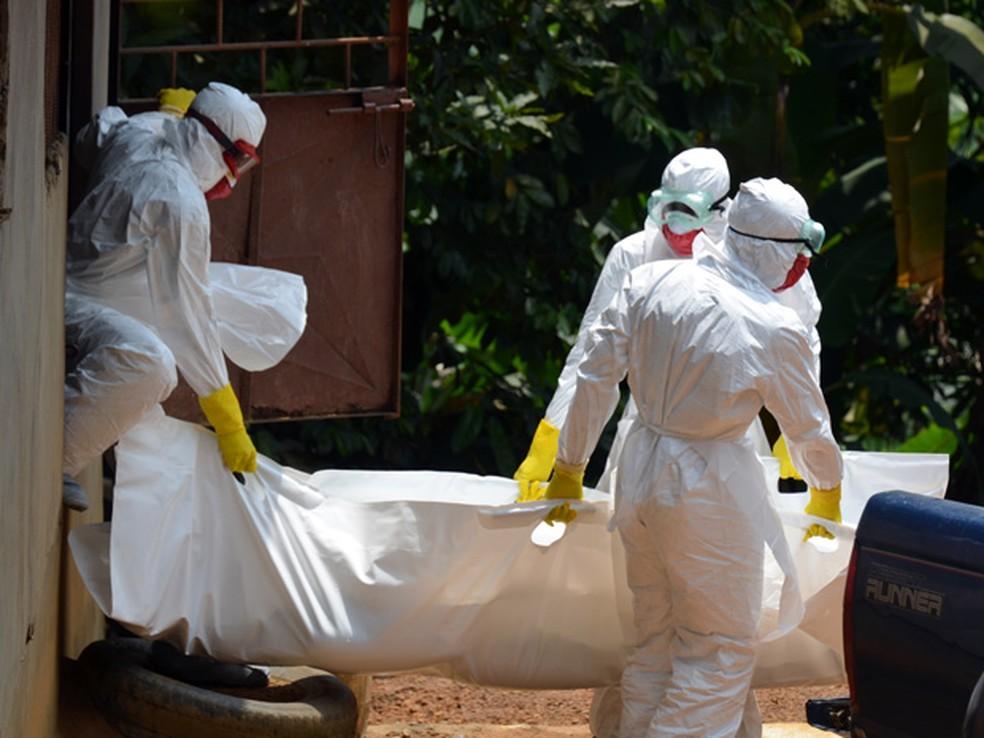 Trabalhadores da Cruz Vermelha usando roupa especial carregam o corpo de uma vítima do vírus ebola em Monróvia, na Libéria (Foto: AFP Photo/Zoom Dosso)