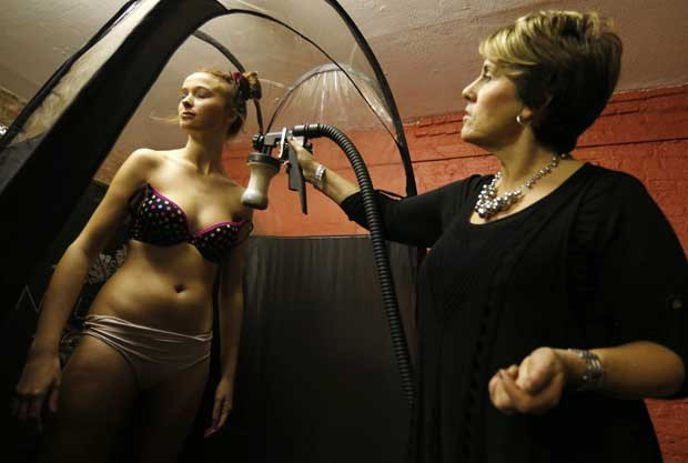 Modelos utilizam sprays para se bronzear durante a Semana de Moda de Liverpool (Foto: Suzanne Plunkett/ Reuters)