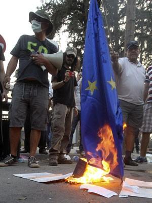 Manifestantes queimam a bandeira de União Europeia em protestos contra a aprovação do pacote do lado de fora do Parlamento (Foto: Andreas Manolis/Reuters)