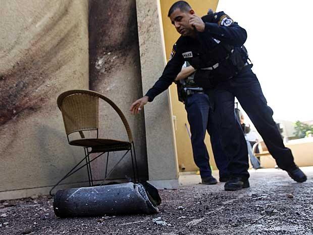 Policiais israelenses examinam restos de um foguete disparado por milicianos palestinos na Faixa de Gaza. (Foto: Amir Cohen / Reuters)