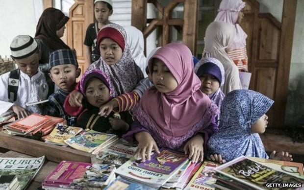 Crianças pegam os livros (Foto: Getty Images/BBC)