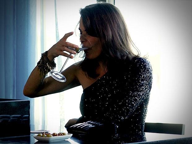 Alexia afoga as mágoas na bebida (Foto: Avenida Brasil / TV Globo)