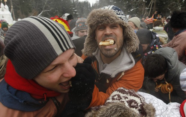 Homem abocanha espécie de rosquinha russa em Novonekrasovsky, a 20 km de Moscou, durante celebração do Maslenitsa (Foto: Maxim Shemetov/Reuters)