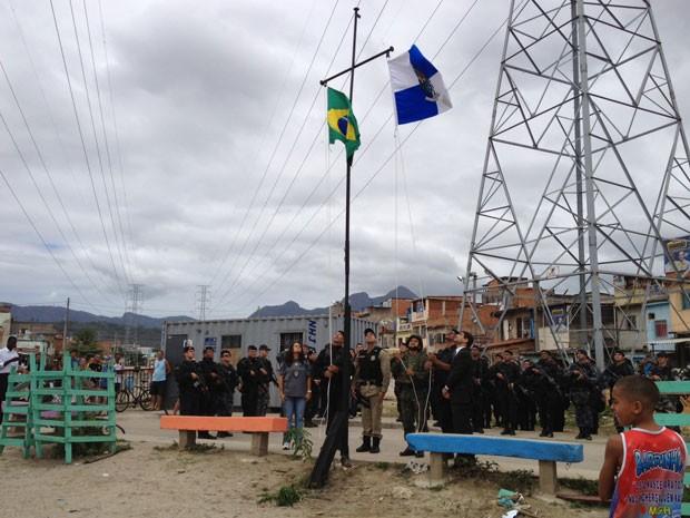 As bandeiras do Rio de Janeirox e do Brasil foram hasteadas por policiais civis,  do Bope e militares na Rua Nossa Senhora dos Navegantes, na Favela de Manguinhos, por volta das 10h deste domingo (14), como sinal de que o território foi tomado pelas força (Foto: Marcelo Ahmed/G1)