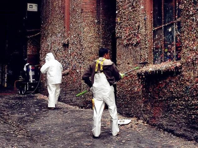 Limpeza das paredes cobertas de chicletes multicoloridos