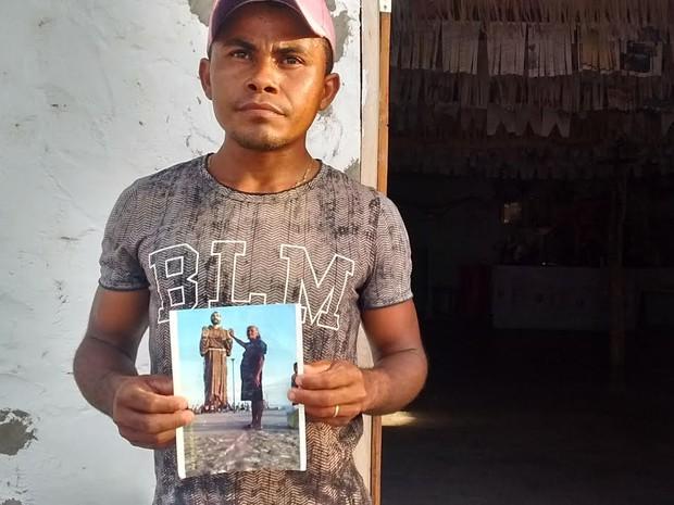 Pedro Vinícius segura a foto da avó, uma das vítimas da chacina (Foto: Catarina Costa)