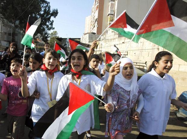 Crianças erguem bandeiras palestinas no campo de refugiados de Shatila na terça-feira (15), marcando o 64º aniversário do Nakba - data que lembra a criação do estado de Israel e suas consequências (Foto: Sharif Karim/Reuters)