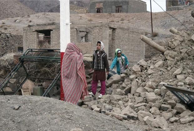 Família iraniana anda sobre pos destroços de casa destruída por terremoto no Irã nesta quinta-feira (6) (Foto: AFP)