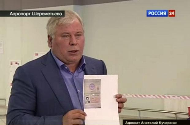 O advogado russo  Anatoly Kucherena mostra cópia do documento temporário de Snowden, em imagem da TV russa (Foto: AP)
