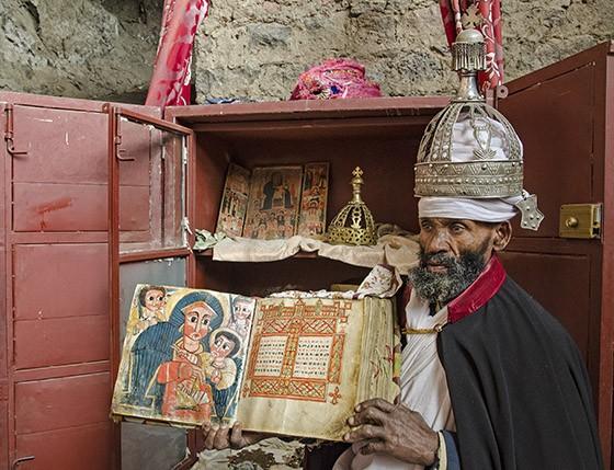 Já com a coroa na cabeça, Abebe mostra as pinturas de um dos livros sagrados que fazem parte do acervo da igreja Na'akuto La'ab (Foto: © Haroldo Castro/ÉPOCA)