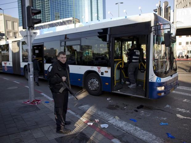 Policial observa local onde homem atacou passageiros de um ônibus em Tel Aviv (Foto: Oded Balilty/AP Photo)