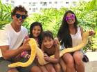 Aline Riscado posa com Felipe Roque e filho segurando cobra gigante