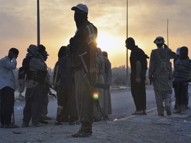 Membros do EIIL fazem guarda em ponto da cidade de Mossul, no norte do Iraque nesta quarta (11) (Foto: REUTERS/Stringer)