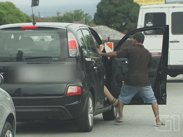 Assaltante tenta tirar passageira de dentro do carro  (Foto: Reprodução/G1)
