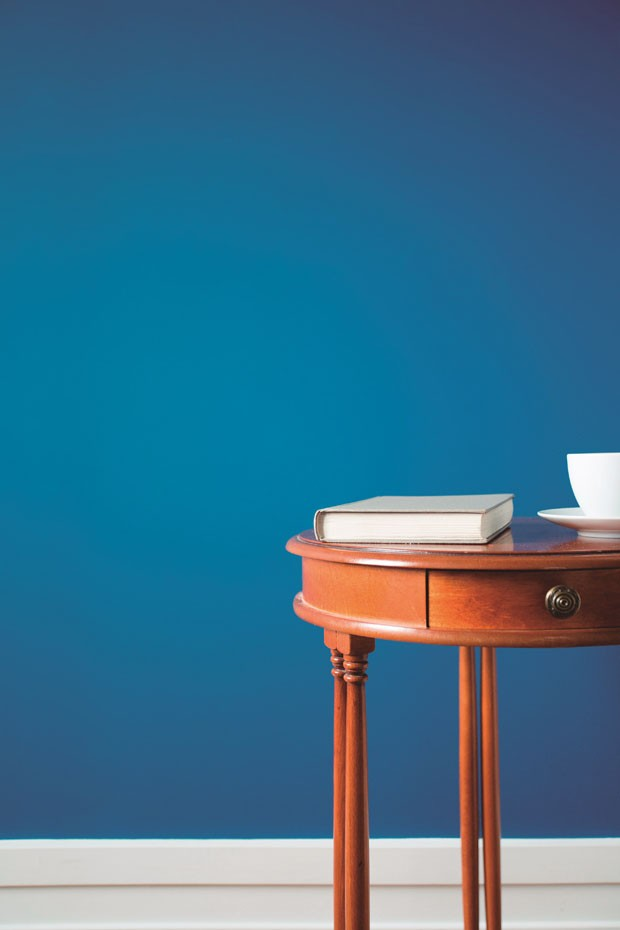 Round wooden coffee table on blue background (Foto: Getty Images/iStockphoto)