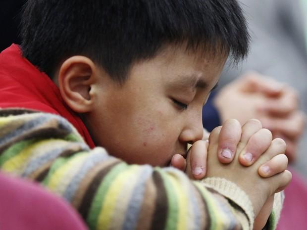 Um menino norte-coreano, desertor, reza, em Seul, pela paz e reunificação da península coreana durante culto em igreja, neste domingo (7) (Foto: Reuters)