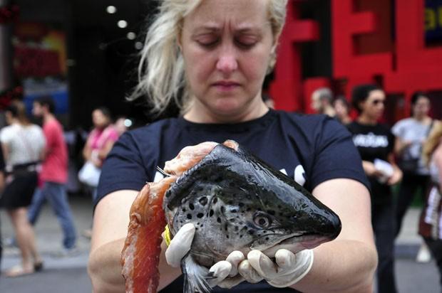 Mulher segura cabeça de peixe durante ato na Avenida Paulista. (Foto: Cris Faga/Estadão Conteúdo)