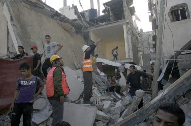 Palestinos observam estragos provocados por bombardeios a casa de militante do Hamas nesta terça-feira (20) em Rafah, na Faixa de Gaza (Foto: AP)