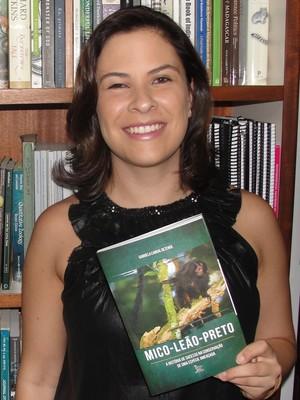 A bióloga Gabriela Rezende com seu livro (Foto: Divulgação)