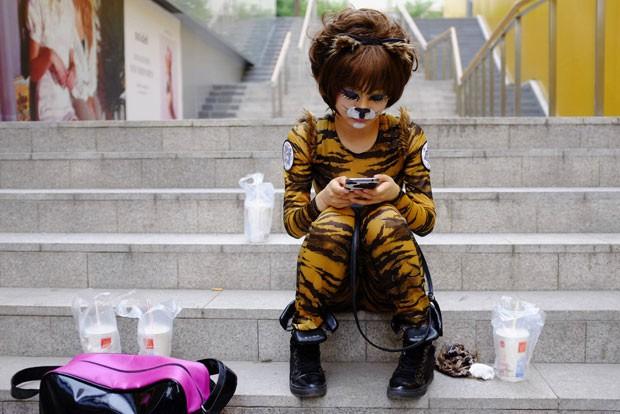 Ativista vestida de cão usa aparelho celular nesta quinta-feira (20) em Pequim, na China (Foto: Jason Lee/Reuters)