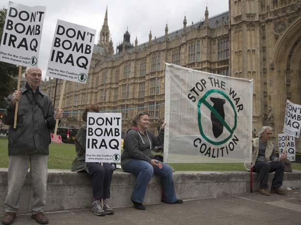 Manifestantes protestam foram do parlmaneto britânico nesta sexta-feira (26) contra ação militar do Reino Unido no Iraque (Foto: REUTERS/Neil Hall)