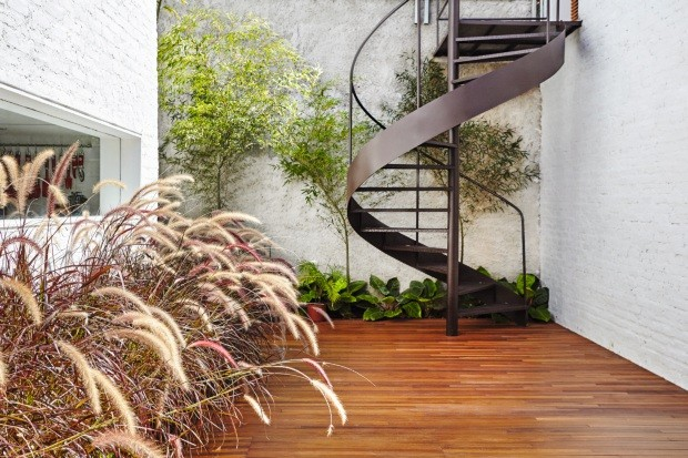 Lateral. Rente ao muro, filodendros-lua-clara e bambus-mossô. O maciço de capim-do-texas-rubro soma movimento e textura ao quintal (Foto: Ilana Bessler / Divulgação)
