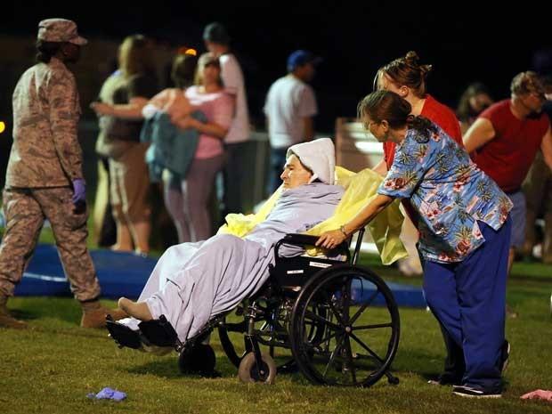 Equipes de emergência ajudam uma idosa em uma escola local. (Foto: Rod Aydelotte / Waco Tribune Herald / Via Ap Photo)