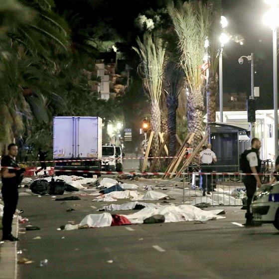 Policial guarda cena do crime ao lado dos corpos das vítimas estirados na Promenade des Anglais,em Nice (Foto:  Franck Fernandes/Maxppp via ZUMA Press)