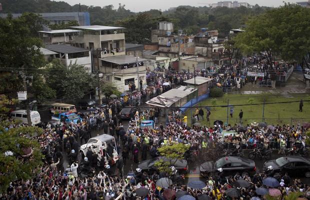 Moradores se aglomeram para acompanhar a passagem de Francisco no papamóvel pelas ruas da favela de Varginha, no Complexo de Manguinhos (Foto: AP Photo/Felipe Dana)