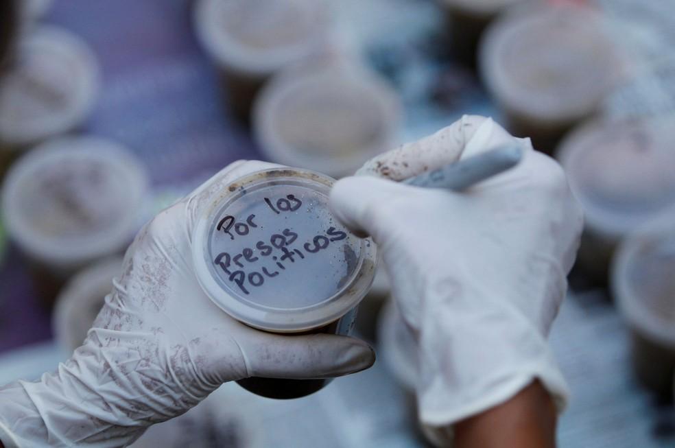 """Mulher escreve """"Pelos presos políticos"""" em frasco cheio de fezes, os chamados """"cocotov"""", durante manifestação na Venezuela  (Foto: Christian Veron/Reuters)"""