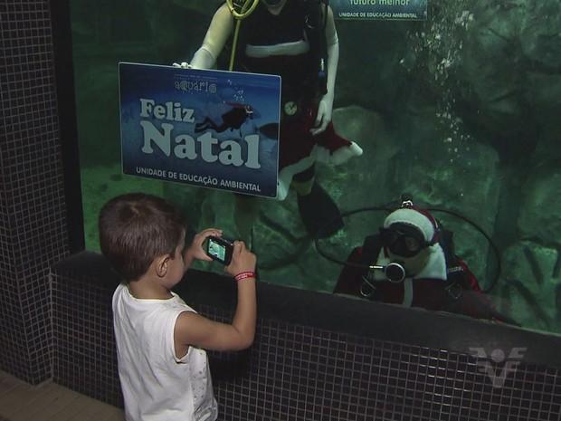 Menino aproveita para registrar foto do Papai Noel e da Mamãe Noel (Foto: Reprodução / TV Tribuna)