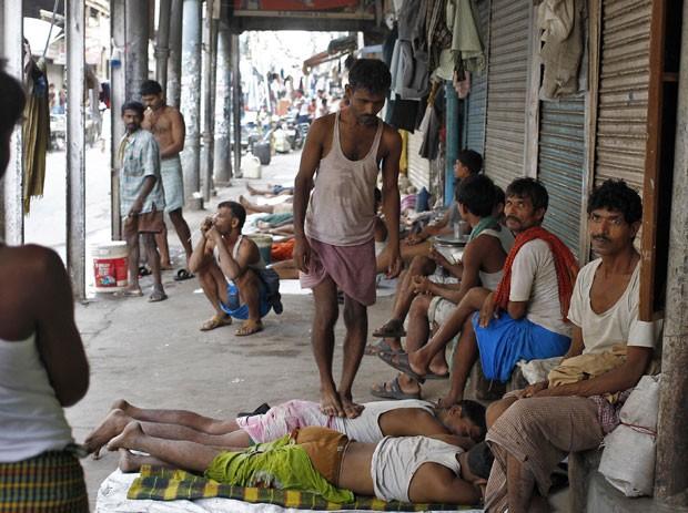 Trabalhador improvisou uma massagem ao pisar sobre as costas de colegas (Foto: Anindito Mukherjee/Reuters)