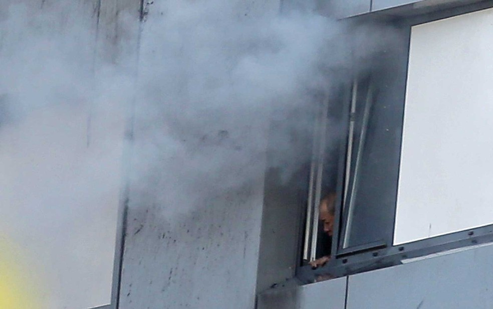 Um homem preso da Grenfell Tower olha para fora enquanto fumaça sai pela janela (Foto: Daniel Leal-Olivas / AFP Photo)