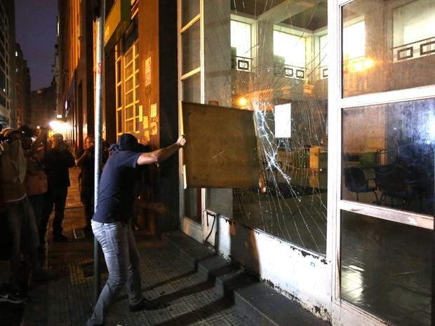 Mascarado quebra fachada de banco no centro de SP (Foto: Eduardo Anizelli/Folhapress)