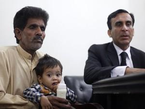 Muhammad Yasin segura o neto de apenas 9 meses durante audiência neste sábado (Foto: Mohsin Raza/Reuters)