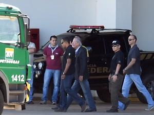 José Dirceu, ex ministro da Casa Civil, é acompanhado por policiais até o avião antes de embarcar em um vôo para Curitiba, onde irá se juntar aos demais presos da Operação Lava Jato (Foto: Evaristo Sa/AFP)