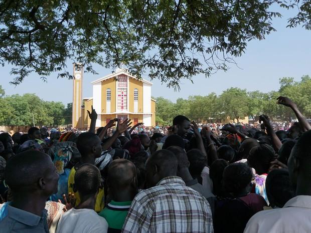 Civis refugiados em catedral católica de Juba recebem fichas para trocar por alimentos e cobertores fornecidos por agências humanitárias, na sexta (15) (Foto: Peter Martell/AFP)