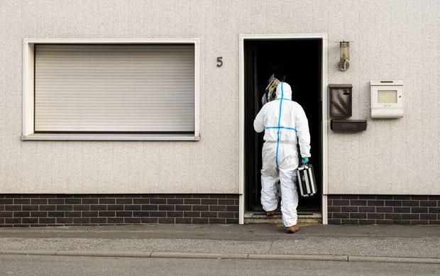 Investigador entra em casa em Wallenfels onde corpos de bebês foram encontrados nesta sexta-feira (13) (Foto: Nicolas Armer/dpa via AP)