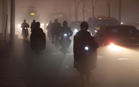 Motociclistas dirigem em meio a ar poluído em Pequim, China (Foto: ChinaFotoPress/ChinaFotoPress via Getty Images)