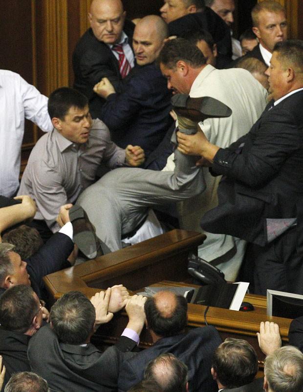 Puxado pelo adversário, um parlamentar acabou caindo do outro lado de uma bancada (Foto: Reuters/Stringer)