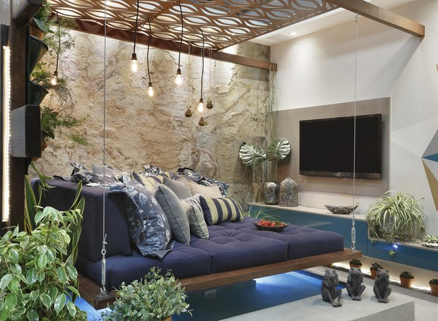"""O """"Espaço Vivência e Convivência"""", projetado por Virginnia Fraga e May Lee Chaves conta com um sofá suspenso sobre o espelho d'água. A iluminação automatizada permite escolher a luz ideal para a varanda coberta, que pode ser utilizada de inverno a verão (Foto: Divulgação)"""