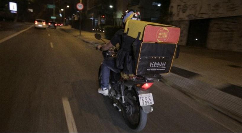 Entregador com a bolsa térmica do Delivery Reverso acoplada à bolsa do restaurante (Foto: Reprodução)