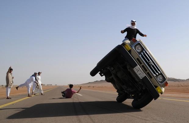Jovem acena após carro trafegando apenas com duas rodas passar muito próximo a ele. Hobby é considerado comum entre os jovens na Arábia Saudita (Foto: Mohamed Al Hwait/Reuters)