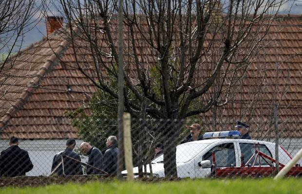 Policiais em frente ao local do crime nesta terça-feira (9) na localidade sérvia de Velika Ivanca (Foto: Reuters)