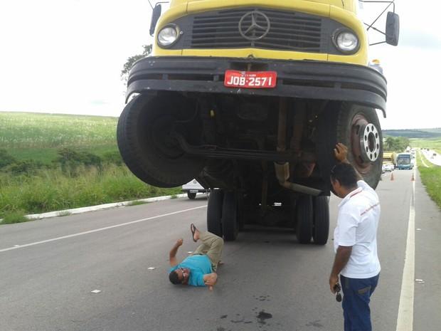 Motorista espera guincho deitado sob a sombra do caminhão (Foto: Danielle Fonseca/TV Globo)