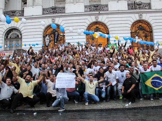 Taxistas comemoram aprovação de projeto de lei que proíbe a circulação de motoristas que façam transporte particular de passageiros, como os associados ao aplicativo Uber, em frente à Câmara Municipal do Rio de Janeiro (Foto: Luiz Souza/Futura Press/Estadão Conteúdo)