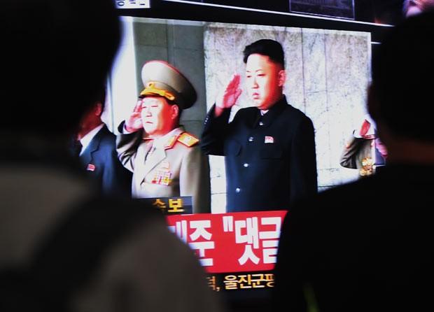 Sul-coreanos observam imagem do líder norte-coreano Kim Jong-un nesta terça-feira (8) (Foto: AP)