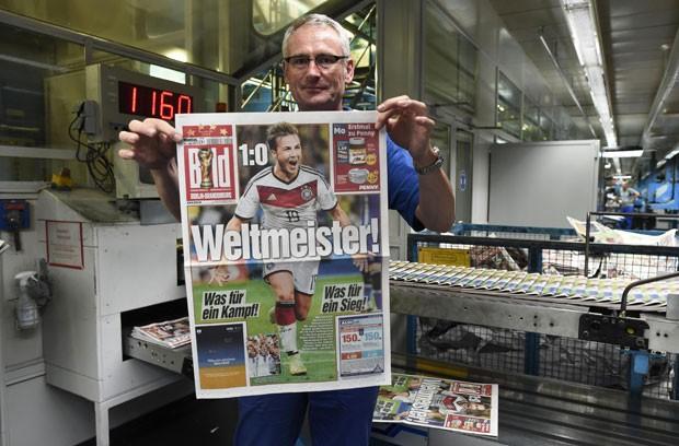 Andreas Schenk, que trabalha na impressão do jornal alemão 'Bild', mostra a primeira página da publicação nesta segunda-feira (14)  (Foto: Fabian Bimmer/Reuters)