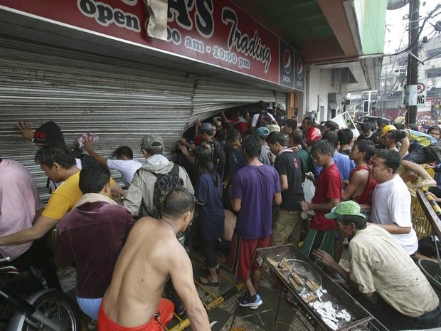 10/11 - Filipinos forçam a porta para saquear uma mercearia em busca de alimentos na cidade de Tacloban, atingida pelo tufão nas Filipinas. (Foto: Aaron Favila/AP)